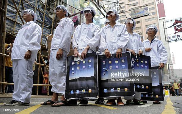Participants dressed up to represent Foxconn workers take part in a protest against Taiwanese technology giant Foxconn which manufactures Apple...