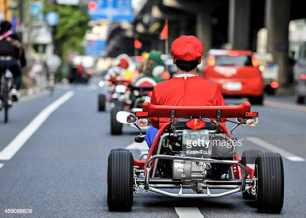 Participants drive around Tokyo in Mario Kart characters for the Real Mario Kart in Tokyo on November 16 2014 in Tokyo Japan The organizer calls for...