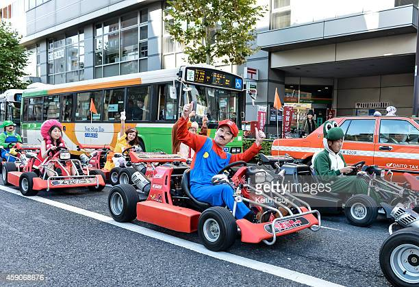 Participants drive around Tokyo in Mario Kart characters for the Real Mario Kart event in Tokyo on November 16 2014 in Tokyo Japan The organizer...