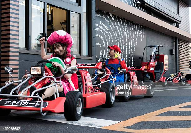 Participants drive through McDonald's drivethru in Mario Kart characters for the Real Mario Kart event in Tokyo on November 16 2014 in Tokyo Japan...