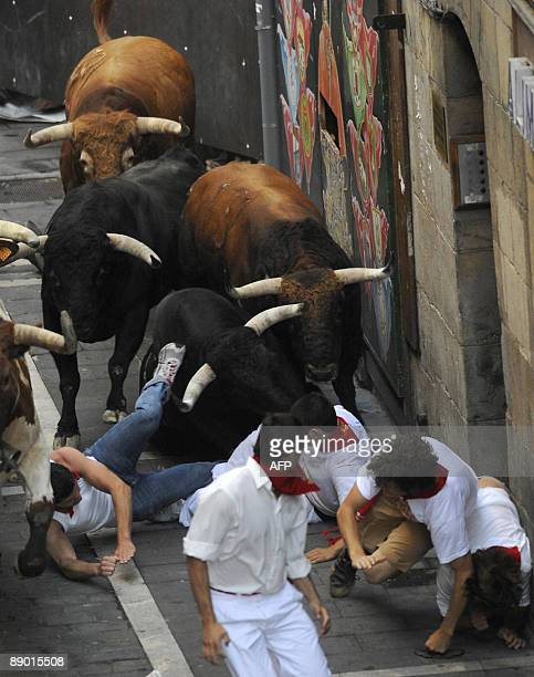 Participants fall in front of Nuñez del Cuvillo fighting bulls on the last San Fermin Festival bull run on July 14 in Pamplona northern Spain The...