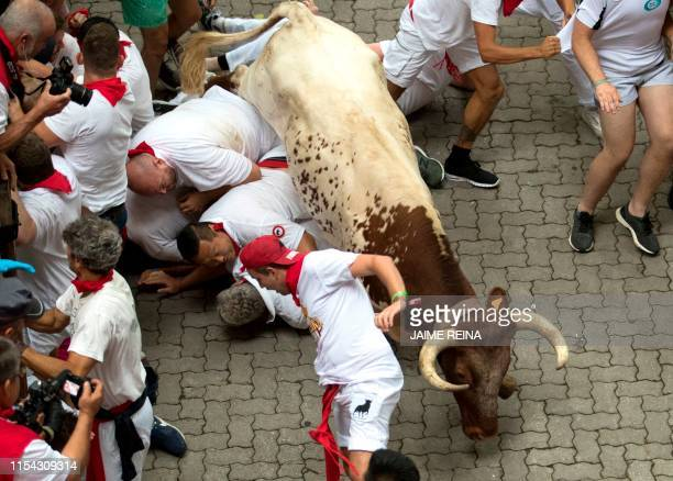 Participants fall next to a Puerto de San Lorenzo fighting bull during the first bullrun of the San Fermin festival in Pamplona northern Spain on...