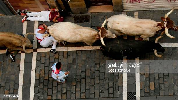 Participants fall next to Nunez del Cuvillo fighting bulls on the fifth bullrun of the San Fermin festival in Pamplona northern Spain on July 11 2018...