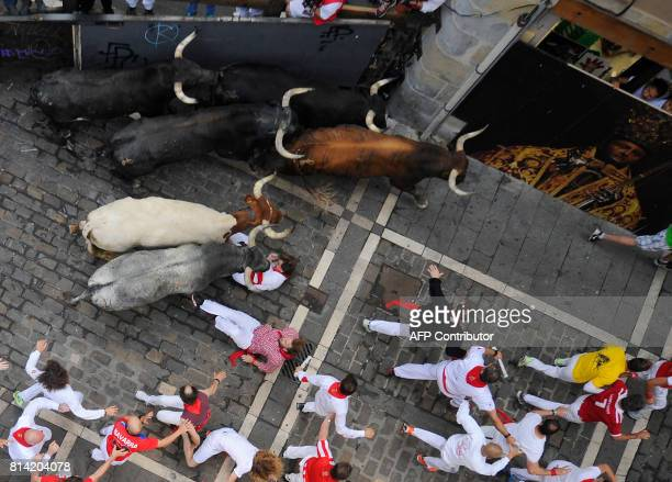 Participants falls as others run ahead of Miura's fighting bulls during the eighth and last bull run of the San Fermin festival in Pamplona northern...