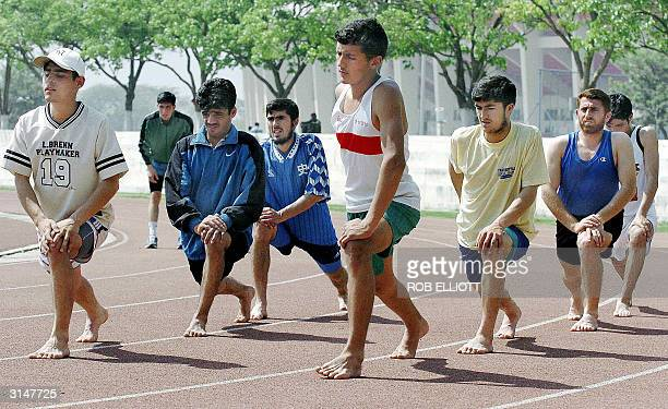 Participants from Afghanistan warmup on the athletics track at the Sports Complex outside Jinnah Stadium in Islamabad 28 March 2004 one day before...