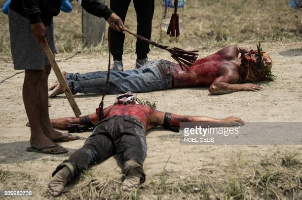 Participants have their bloodied backs whipped with bamboo as part of their penitence during the reenactment of the crucifixion of Jesus Christ for...