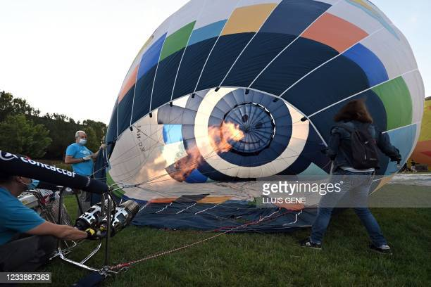 Participants heat the air to inflate a hot-air balloon during the 25th European Hot Air Balloon Festival held in Igualada, 70 km away from Barcelona,...