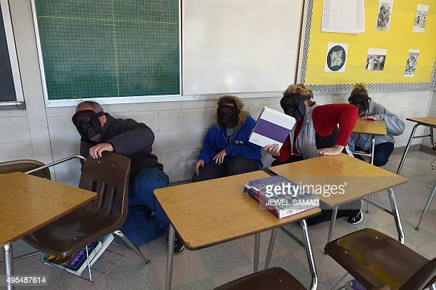 Participants hide from an active shooter during ALICE training at the Harry S Truman High School in Levittown Pennsylvania on November 3 2015 ALICE...