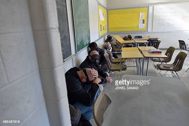 Participants hide from an 'active shooter' during ALICE training at the Harry S Truman High School in Levittown Pennsylvania on November 3 2015 ALICE...