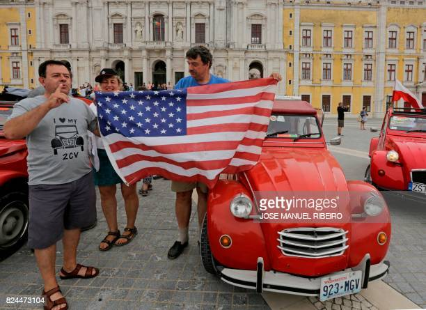 Participants hold a flag after their arrival to the parking area in Mafra after the parade of Citroen classic cars 2CV during the World 2017 2CV...
