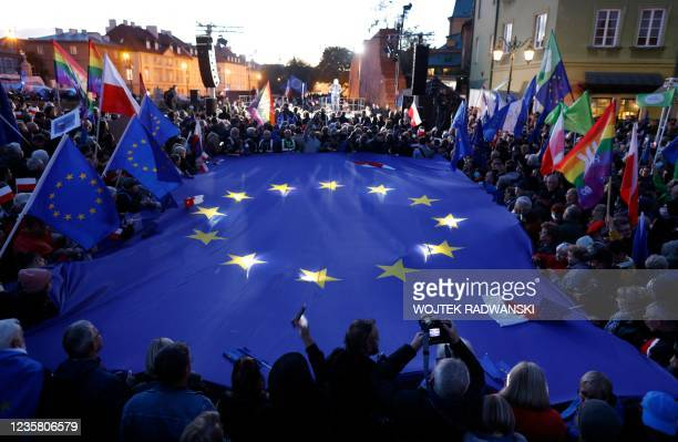 Participants hold a large EU flag as they take part in a pro-EU demonstration following a ruling of the Constitutional Court against the primacy of...