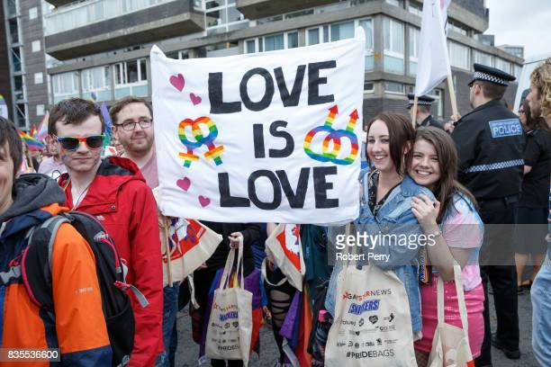 Participants hold a sign that says Love is Love during the Glasgow Pride march on August 19 2017 in Glasgow Scotland The largest festival of LGBTI...