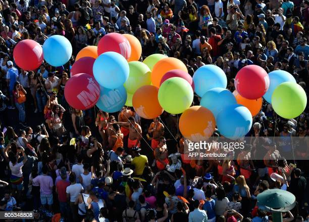 Participants hold big balloons during the WorldPride 2017 parade in Madrid on July 1 2017 Revellers took to the rainbow streets of Madrid today in...