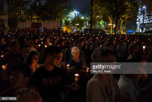 Participants hold candles as the Tiananmen Square banner stands at the background on June 4 2017 in Hong Kong Hong Kong Hong Kong is marking 20 years...