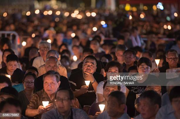 Participants hold candles during a vigil for the 27th anniversary of the 1989 Tiananmen Square crackdown, at Victoria Park in Hong Kong on June 4,...