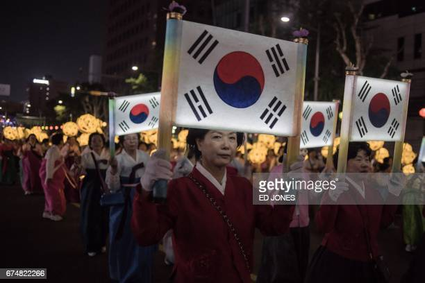 Participants hold illuminated South Korean flags as they march during a lantern parade marking the start of a monthlong 'Lotus Lantern Festival' to...