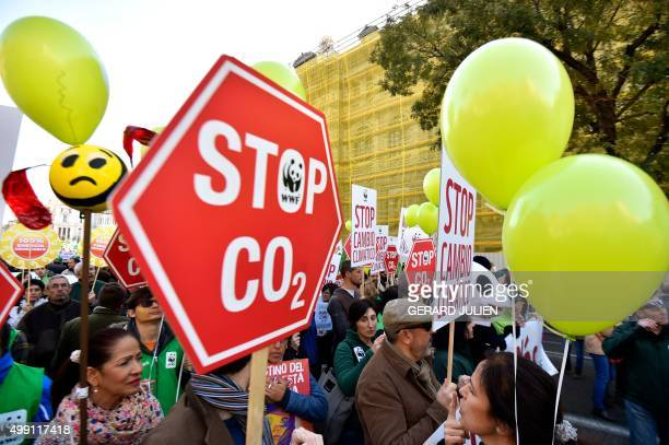 """Participants hold placards as they march during the """"Global Climate March"""" on November 29, 2015 in Madrid, called by environmental NGOs on the eve of..."""