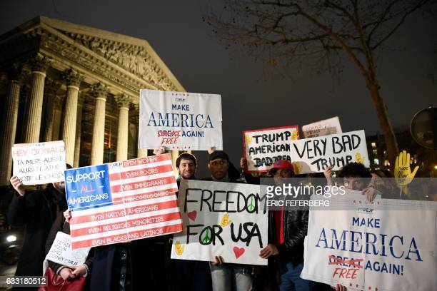 TOPSHOT Participants hold placards reading 'Make America free again' Freedom for USA' and 'Very bad Trump' during a demonstration organized by French...