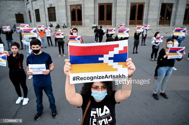 """Participants hold placards with the hashtag """"Recognize Artsakh"""" during a flash mob to support the breakaway Nagorno-Karabakh region in Yerevan on..."""