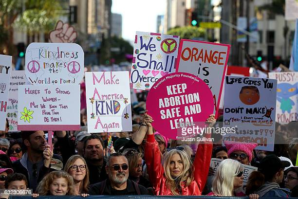 Participants hold signs as they march during the Women's March on January 21 2017 in Los Angeles California Tens of thousands of people took to the...