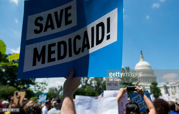 Participants hold signs during the Senate Democrats' rally against Medicaid cuts in front of the US Capitol on Tuesday June 6 2017