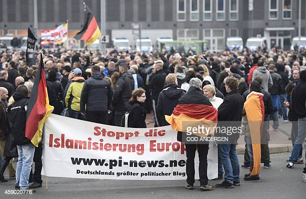 Participants hold up German flags and a banner reading 'Stop Europe's Islamization' during a farright hooligan rally against Islamist extremism under...