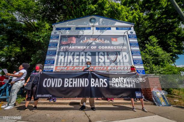 Participants holding a banner reading COVID BEHIND BARS = DEATH at the rally in Rikers Island. Civil rights and racial justice leaders held a rally...