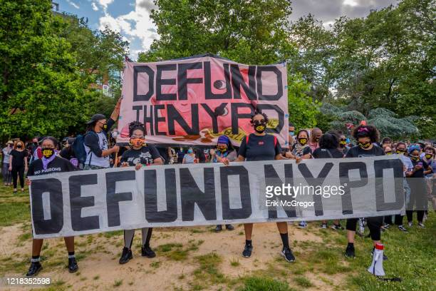 Participants holding a giant Defund NYPD banner Thousands of protesters gathered at Mc Carren Park in Brooklyn for a massive march around...