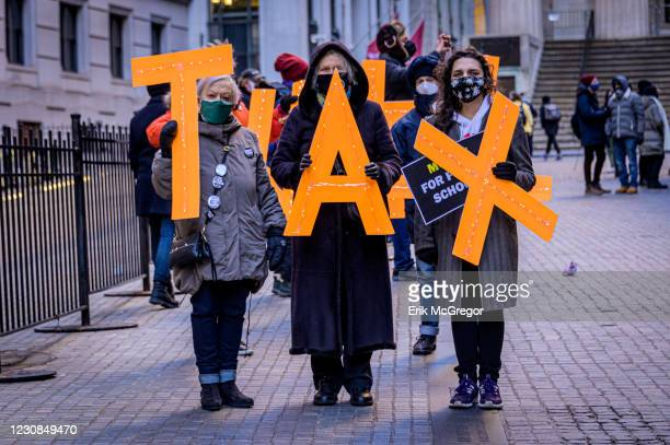 Participants holding letters spelling TAX. In the face of worsening pandemic conditions in the country, a coalition of Activists gathered outside the...