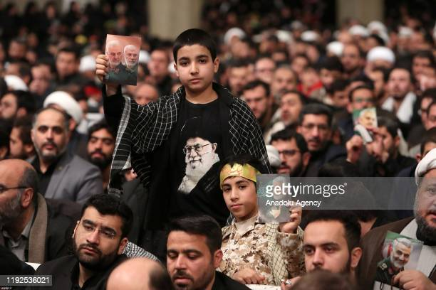Participants holds posters of Iranian commander Qasem Soleimani and Abu Mahdi al-Muhandis, vice president of the Hashd al-Shaabi group as they listen...