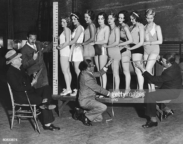 Participants in a beauty contest are measured by a team of experts, circa 1935.