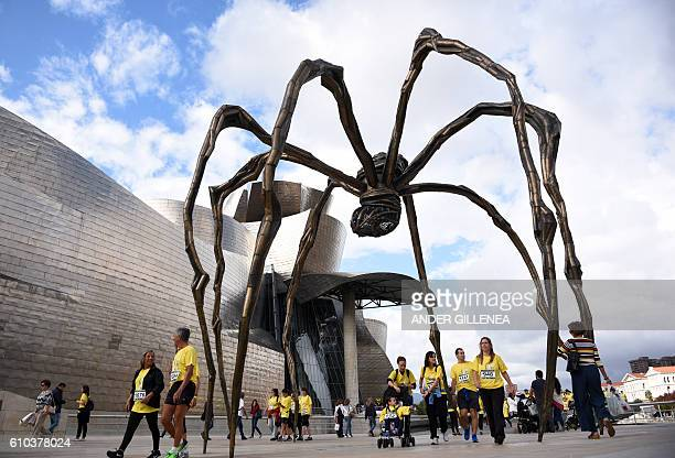 Participants in a charitable run walk through French artist Louise Bourgeois' sculpture 'Maman' next to the Guggenheim Bilbao Museum during the...