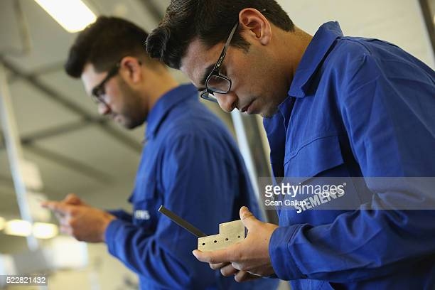 Participants in a jobtraining program for refugees work with metal at a Siemens training center on April 21 2016 in Berlin Germany Siemens is...