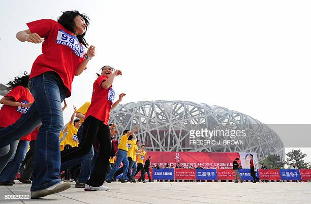 """Participants in a long-distance race run past the National Stadium, also known as the """"Bird's Nest"""" for its design on April 30, 2008 in Beijing,..."""