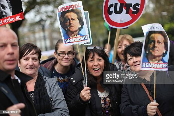 Participants in a TUC march in protest against the government's austerity measures hold up placards featuring pictures of the merged faces of current...