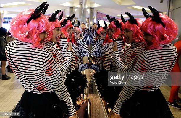 Participants in costume check their outfits in front of a mirror during Halloween celebration at Shibuya district on October 31 2016 in Tokyo Japan