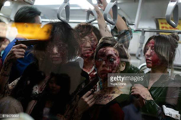 Participants in costume pose for a photograph as they ride on a train after Halloween celebrations at Shibuya district on October 31 2016 in Tokyo...
