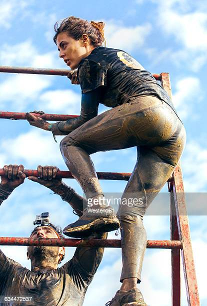 Participants in extreme obstacle race climbing over hurdle