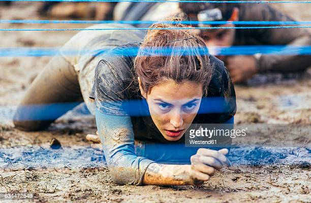 participants in extreme obstacle race crawling under electric wire - superando as dificuldades - fotografias e filmes do acervo