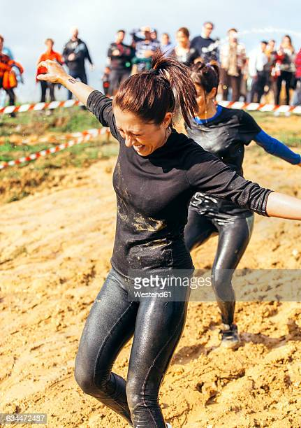 participants in extreme obstacle race, running through mud - 得点打 ストックフォトと画像