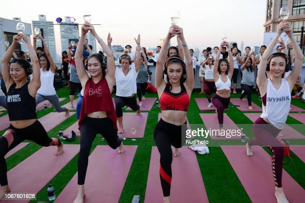 Participants in Silent Wine Yoga class perform a yoga exercise with a wine glass in Bangkok at at Compass Sky View hotel in Bangkok Thailand 02...