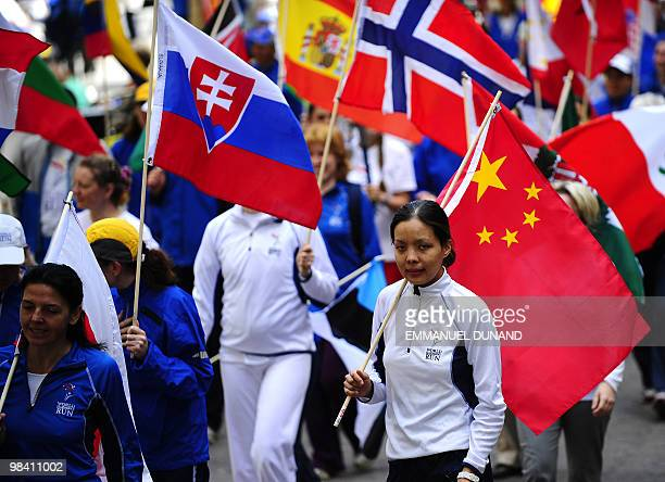 Participants in the 2010 World Harmony Run hold torches and flags at the start of the worldwide relay in New York, April 12, 2010. Founded in 1987 to...