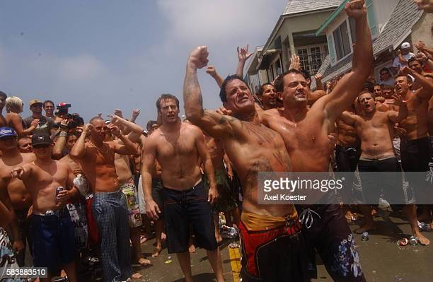 Participants in the annual Fourth fo July Hermosa Beach Ironman festival party after a short run and paddle on their surf boards. The actual...