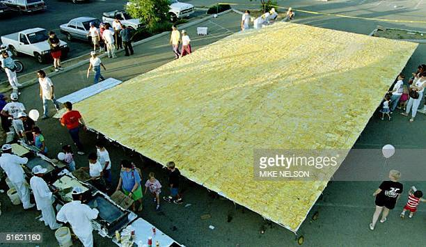 Participants in the effort to break the world's record for the largest omelette finish up the gigantic cheese omelette which took five chefs working...