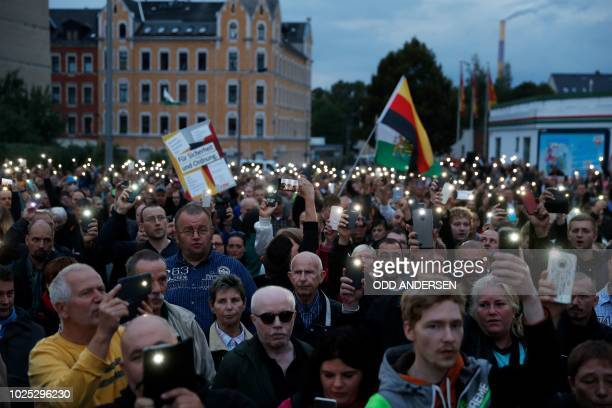 """Participants in the far-right group """"Pro Chemnitz"""" protest rally use their cell phones as lights as they sing the national anthem at the entrance to..."""