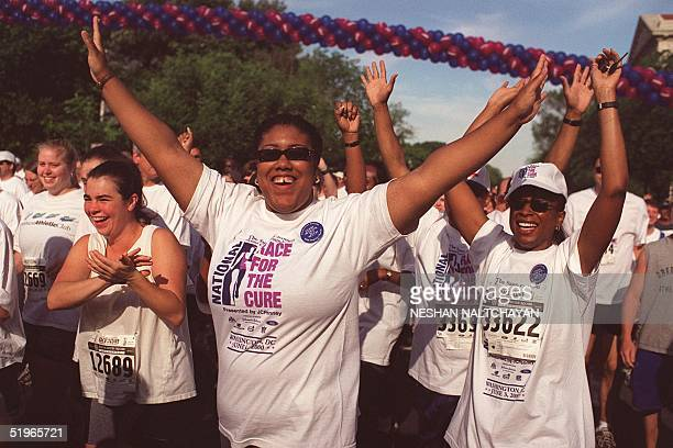 Participants in the five kilometer Race for the Cure cross the finish line 03 June 2000 in Washington, DC. The race raises money for breast cancer...