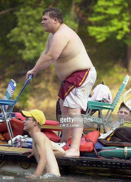 Participants in the Oconee River Raft Race make their way down the river during the Seventh Annual Summer Redneck Games July 6, 2002 in East Dublin,...
