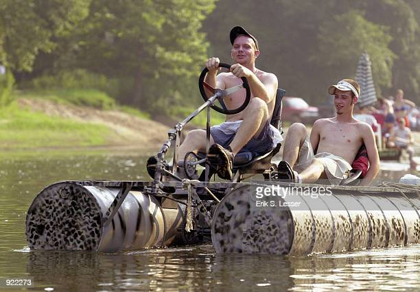 Participants in the Oconee River Raft Race peddle their raft down the river during the Seventh Annual Summer Redneck Games July 6 2002 in East Dublin...