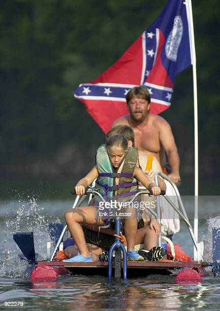 Participants in the Oconee River Raft Race peddle their raft down the river during the Seventh Annual Summer Redneck Games July 6, 2002 in East...