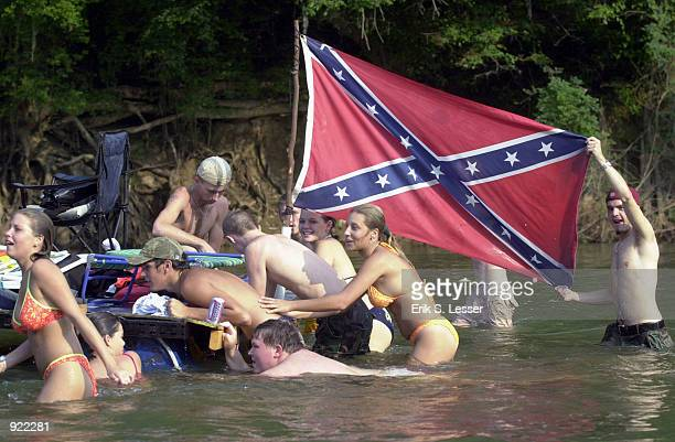 Participants in the Oconee River Raft Race push their raft down the river during the Seventh Annual Summer Redneck Games July 6, 2002 in East Dublin,...